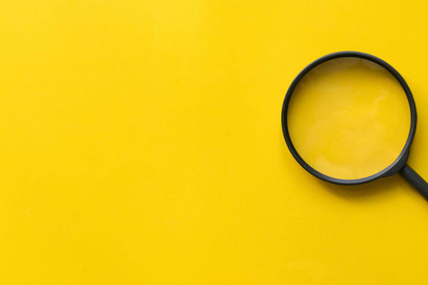 stock art with yellow background and black magnifying glass to the right