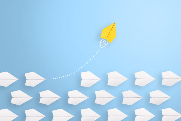 yellow paper airplane leading among white